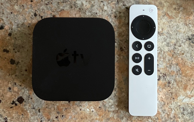 Apple TV 4K box and remote on stone counter top.