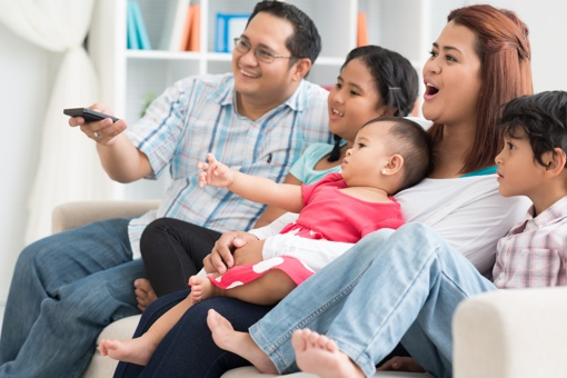 Family of five watching TV on couch