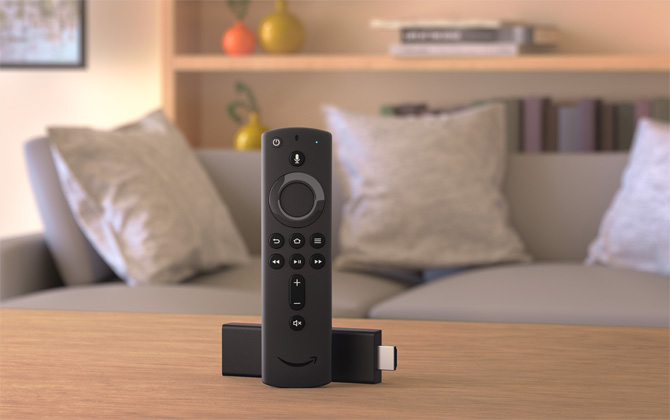 Fire TV Stick on table with sofa and bookshelf in the background