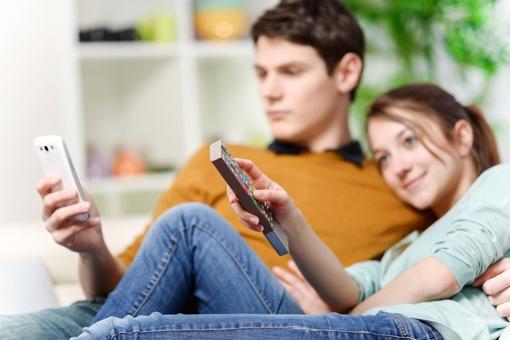 Man watching smartphone; woman watching TV