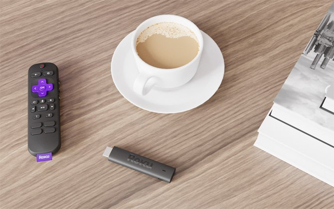 Roku Voice Remote Pro on the left, with a coffee cup in the middle, the Roku Streaming Stick 4k Plus below the coffee cup and a black-and-white print on the right side. Everything is on a wooden table.