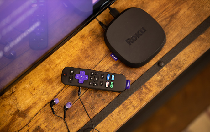 Roku Ultra streaming box with remote control that has headphones plugged in.