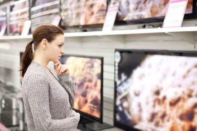 Woman looking at TVs