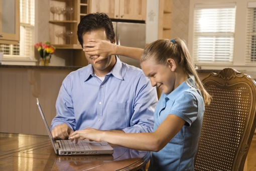 Girl hides father's eyes from computer screen
