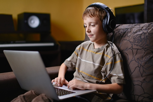 Boy using a laptop with headphones