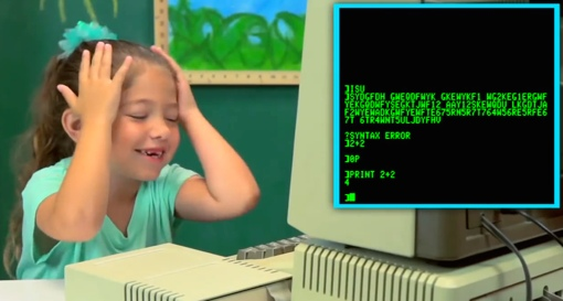 A young girl reacts to an old monochrome computer