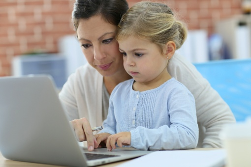 Mom and daughter using computer at home
