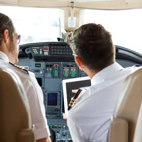 Pilots in plane cockpit using tablet