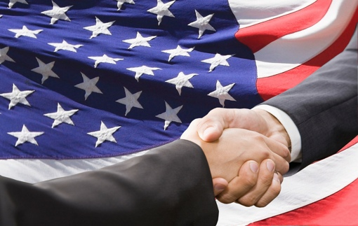 Handshake with American flag backdrop