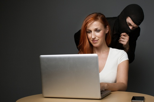 Thief looking over woman's shoulder at computer