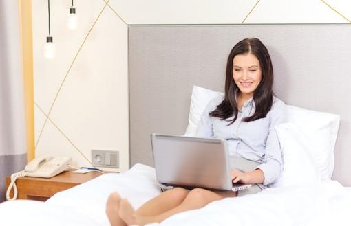 Businesswoman using computer in hotel room