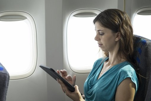 Woman with tablet on plane