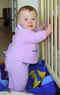 baby standing against crib
