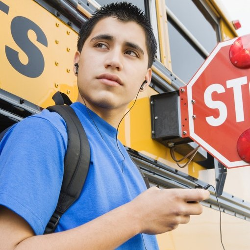 Boy next to a school bus with headphones