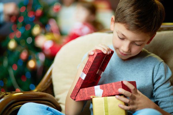 boy opening present via Shutterstock
