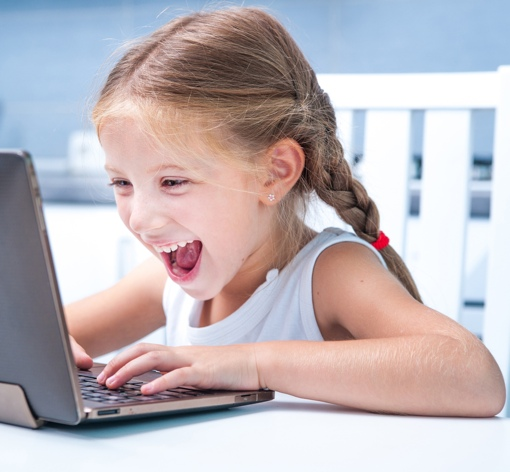 Child happily using a laptop