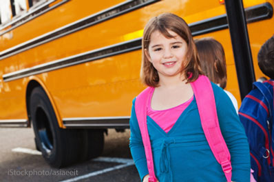 girl getting on school bus