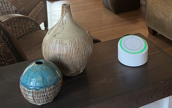 AerNos AerHome sitting on a wood table with two ceramic vases.