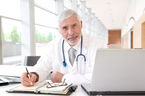 Doctor sitting at computer practicing telemedicine