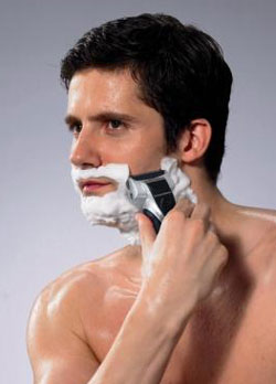 Man using electric shaver with shaving cream