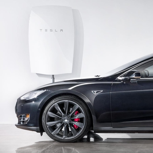 Tesla Powerwall battery mounted next to a car
