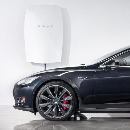 Tesla Powerwall battery mounted next to a car