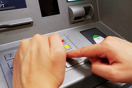 Hand shielding the entry of a PIN at an ATM