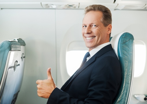 Businessman giving thumbs up on airliner