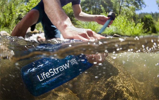 LifeStraw Go Water Filtering Bottle open and submerged in a stream. The the person's other hand is the top show the top with the filter straw.