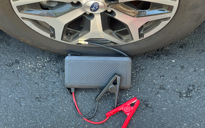 Mophie Powerstation Go Rugged with Air Compressor shown with jumper cables in front of a car tire.