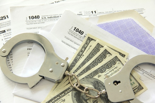 Handcuffs and cash on top of a pile of IRS forms