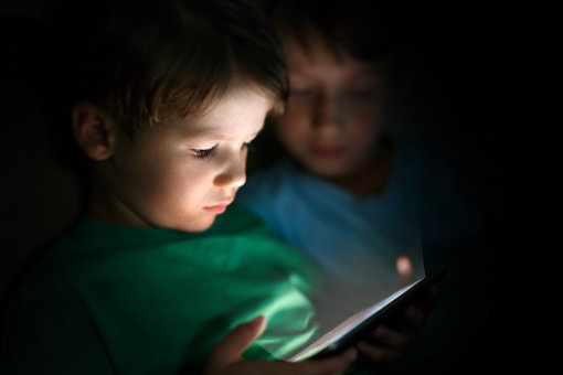 Child playing on tablet in the dark