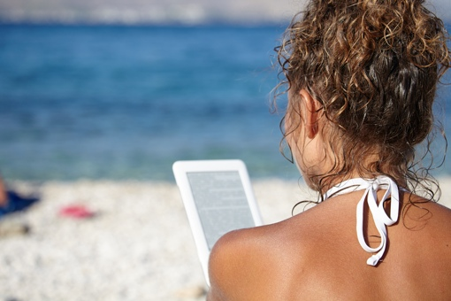 Woman on beach with e-reader