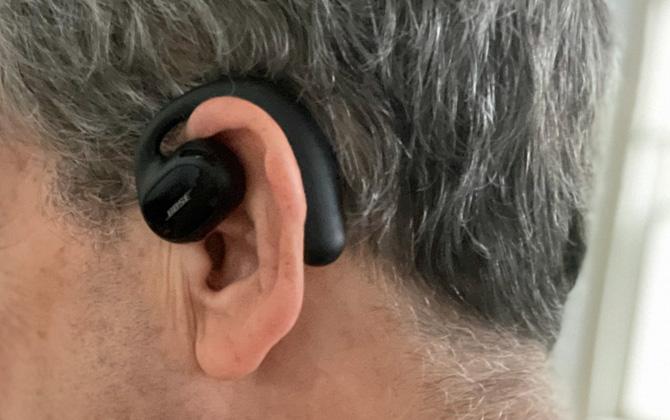 Bose Sport Open Earbud worn on model. Seen here in closeup on ear.