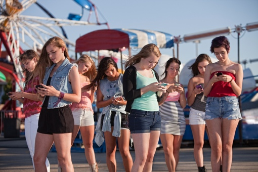 Girls at amusement park text messaging each other