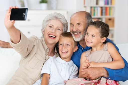 Grandparents taking smartphone selfie with grandkids