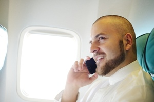 Man making a phone call on a plane