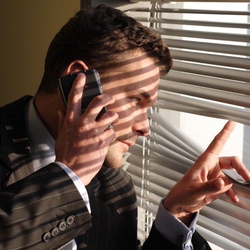 Man on phone looking through blinds