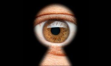 Man peeking through keyhole