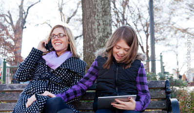 Mother and daughter using mobile devices