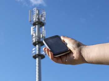 Smartphone held next to cell tower