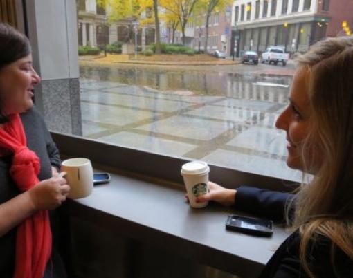 Women using wireless phone charging stations at Starbucks
