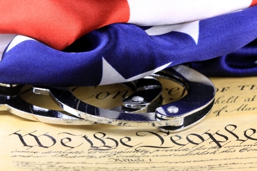 Handcuffs and American Flag on a copy of the U.S. Constitution