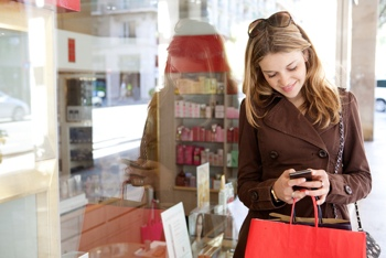 Woman using her smartphone while shopping